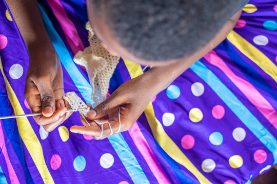 young african boy learning to knit
