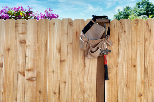 New wooden fence with tool belt and pouch hanging from main post