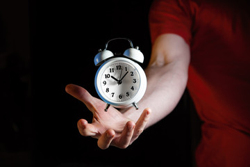White retro alarm clock hovering above Caucasian male hand against dark background with copy space