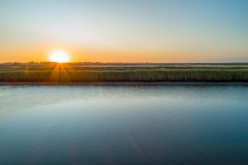 Aerial view of sunset over horizon with river tall reeds and copy space