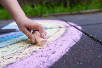 Closeup of child hand drawing rainbow using colorful chalk