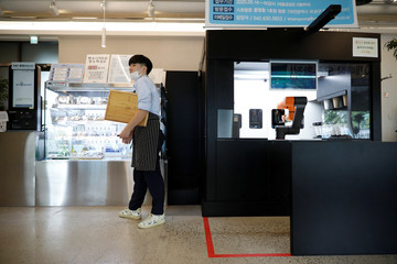 An employee stands next to a barista robot that takes orders, makes coffee and brings the drinks straight to customers in Daejeon