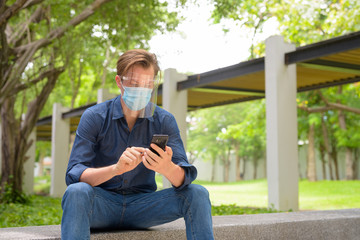 Obraz Young man using phone with mask and face shield while sitting at the park - fototapety do salonu