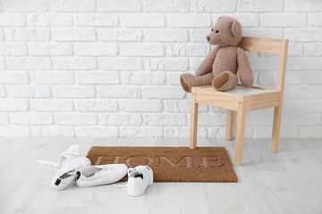 Door mat, chair with toy and shoes near brick wall