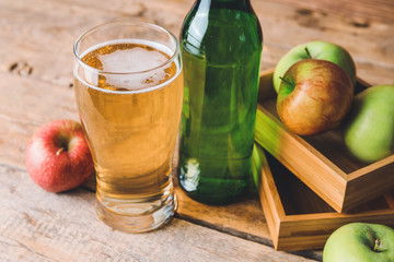 Bottle and glass of apple cider on table