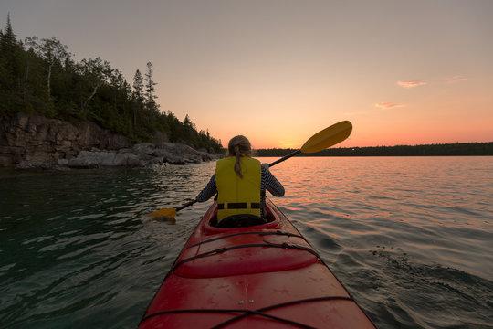 Woman Kayaking In Lake Against Sky During Sunset