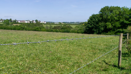 Barbed wire fence views in to farm fields with small village in the distance