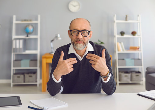 Mature man with a gray beard looks at the camera, speaks with his partner sitting at a table in the office at home.