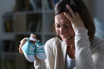Sad mother missing her daughter after miscarriage at night at home