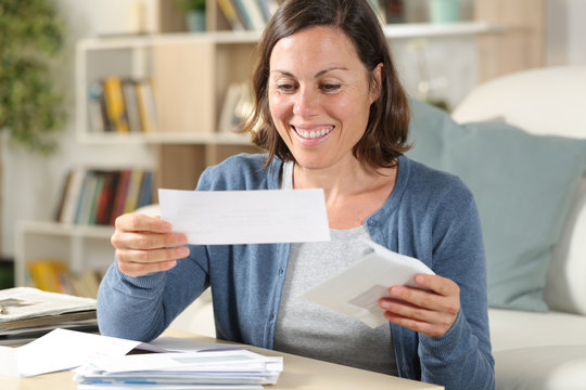 Happy middle age woman opening receipts at home