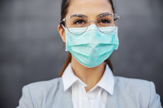 Portrait of gorgeous businesswoman with protection mask on standing outdoors. Protection form corona virus concept.
