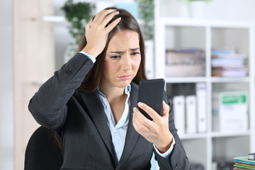 Sad worried executive discovers mistake on phone at office