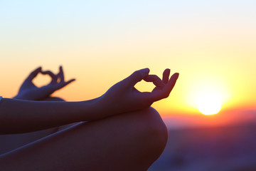 Woman hands at sunset relieving stress doing yoga