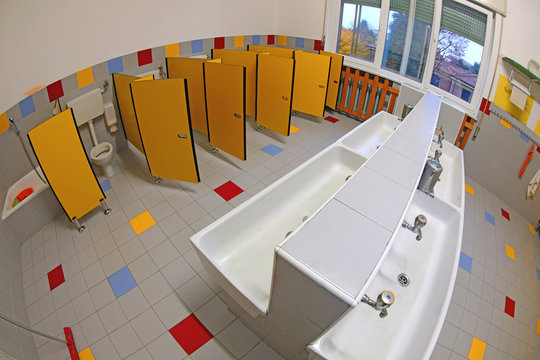 bathroom of a kindergarten without children with sinks and yello
