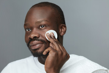 Face Skincare. Male African Model Cleans Facial Skin With Round Cotton Pad. Beauty Treatment Routine For Man.