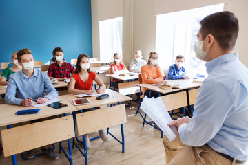 education, pandemic and health concept - group of students in masks and teacher at school