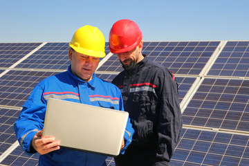 Green energy, power plant and two electricians with laptop