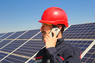 Worker in a red helmet makes a phone call in the solar power plant