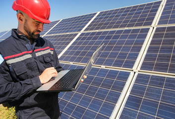Worker in a red helmet and laptop in the solar power plant