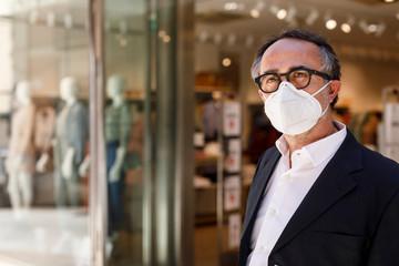 uomo con occhiali neri vestito elegante  e con mascherina facciale Kn95 davanti a un negozio nelle...