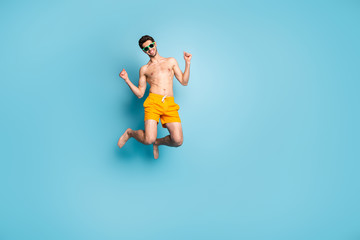 Full length body size view of his he nice attractive cheerful cheery guy in swimming shorts jumping having fun isolated on bright vivid shine vibrant green blue turquoise color background