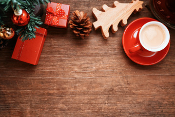 Top lay out gift boxse and pine cone and red coffee cup decorate under chriatmas tree , picture have space for idea.