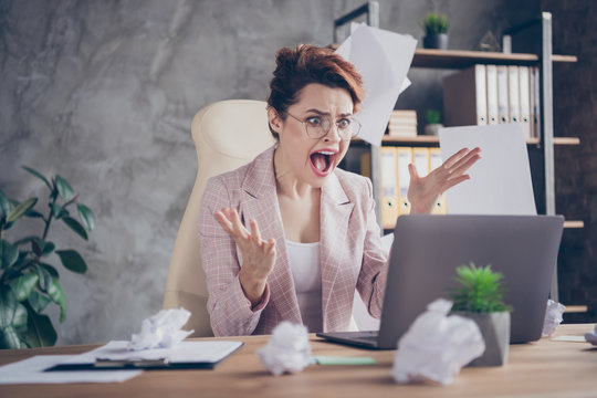 Close-up portrait of nice attractive desperate mad lady throwing documents yelling burn-out looking at screen blunder mistake at modern industrial concrete wall style interior workplace workstation