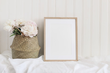 Beige blank wooden picture frame mockup. Artistic table still life composition with pink peony flowers in straw basket. White wooden wall background. Empty copyspace, rustic design.