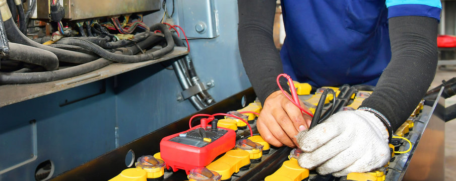 Technician inspection holding Battery Capacity Tester Voltmeter.for service maintenance of industrial to engine repair