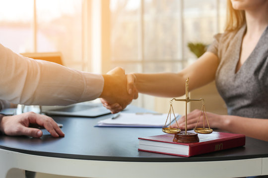 Man and lawyer shaking hands in office