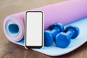 Fitness at home, smartphone app for online training, dumbbell weights and mat. Blank empty screen space, Set of workout inventory. Body care, healthy lifestyle, distance exercising, sport concept