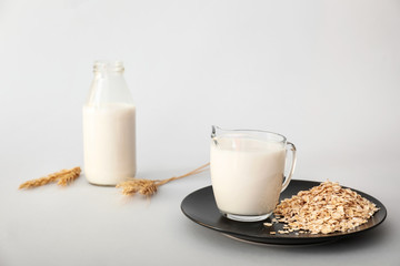 Tasty oat milk on light background