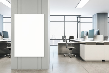 Office interior with blank vertical poster on wall
