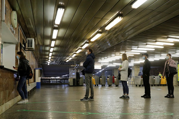 People practice social distancing at a metro station in Kiev