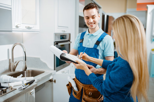 Male plumber and female customer in the kitchen