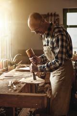 Mature carpenter working in a rustic workshop