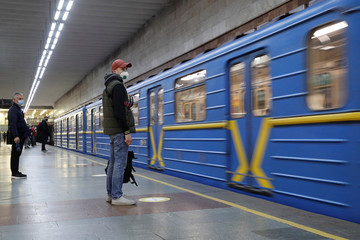 People practice social distancing while waiting for a train at Pozniaky metro station in Kiev