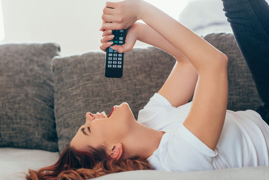 attractive girl singing with remote controller at home during self isolation
