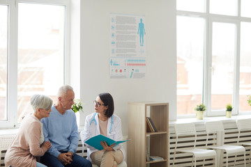 Wide angle portrait of young female doctor talking to senior couple while sitting in reception area...