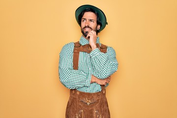 Young handsome man wearing tratidional german octoberfest custome for Germany festival with hand on chin thinking about question, pensive expression. Smiling and thoughtful face. Doubt concept. Fotomurales