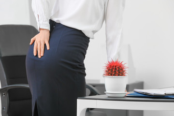 Photo sur Plexiglas Ane Young businesswoman with hemorrhoids in office