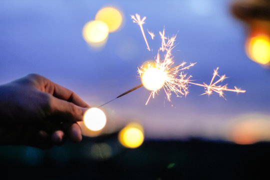 Woman Hand Holding Illuminated Sparkler At Night
