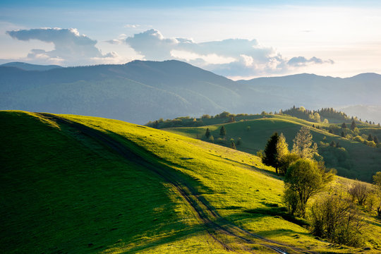 path through countryside fields. beautiful view of rural landscape at sunset. hills rolling down in to the distant valley. clouds on the blue sky in evening light