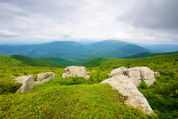 Wall Mural - huge stones in valley on top of mountain ridge. mountain summer landscape. meadow with huge stones among the grass on top of the hillside near the peak of mountain range