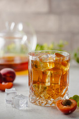 Glass of peach or apricot iced tea with fruit slices against white background