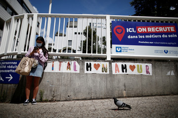 A woman wearing a protective face mask stands next to a slogan written in front of the Robert Debre hospital in Paris