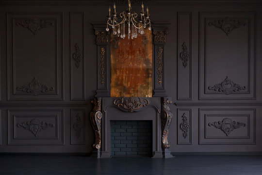 Decorative fireplace, vintage mirror and chandelier in classical black room interior