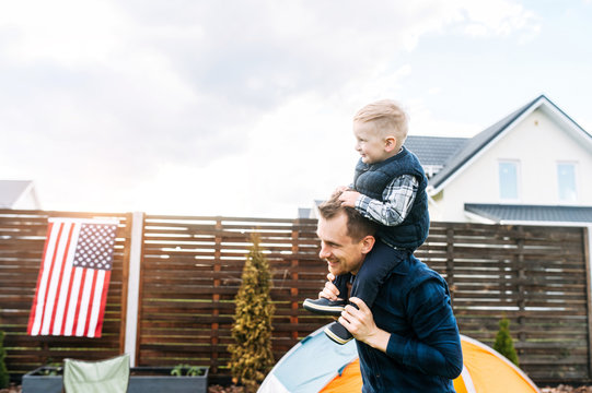 Camping in the backyard. A dad and son set up a tent on a lawn and they are spending time funny together. A boy sits on the shoulders of dad and laughs