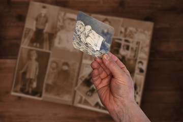 Wall Mural - old man's male hands hold old retro family photos over an album with vintage monochrome photographs in sepia color, the concept of genealogy, memory of ancestors, family ties, childhood memories