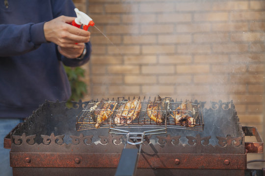 Pouring mackerel roasting on grill with water from spray bottle